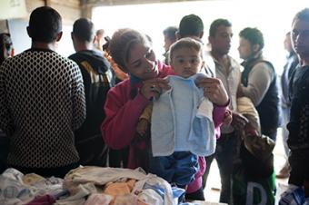 A Syrian woman looks for clothes for her baby at the Mixer House distribution center in Belgrade. Photo by Kira Horvath for CRS