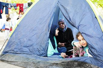 This Syrian girl waits in a tent with her mother, grandmother and sister for a bus that will take them to Hungary. The family, seeking asylum in Germany, has been traveling for more than a month. Photo by Kira Horvath for CRS