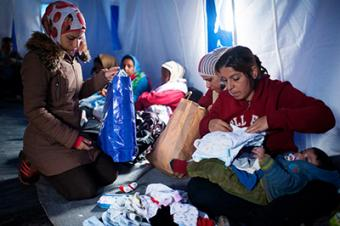 A Syrian woman looks for dry clothes for her baby. Heavy rains made the already harrowing journey to Kanjiza much more difficult. Photo by Kira Horvath for CRS