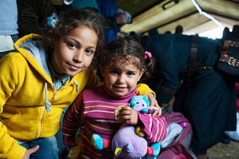 Syrian refugees Omama Basheer, left, and her sister, Rouya, enjoy a respite from their journey at Vasariste. Photo by Kira Horvath for CRS