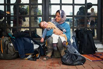 Zaineb plays with her 1-year-old daughter, Maria, at a Belgrade bus station while waiting for transportation to the Hungary border. She had been traveling for 22 days and hoped to reach Sweden where she has a brother. Photo by Kira Horvath for CRS