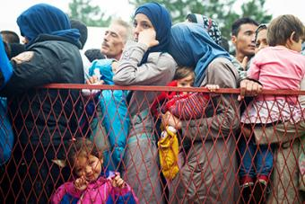 Refugees gather at a park near the Belgrade bus station waiting for transportation to the Hungary border. This year, thousands have fled countries in northern Africa and the Middle East seeking asylum in Europe. Photo by Kira Horvath for CRS