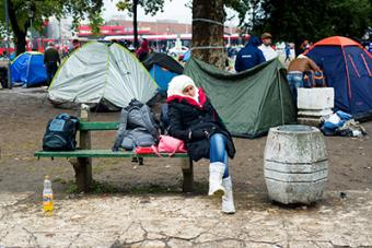 A woman sleeps on a park bench near the Belgrade bus station, where refugees pitch tents and await transportation to the Hungarian border. Photo by Kira Horvath for CRS
