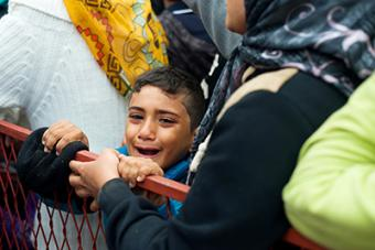 A Syrian boy, jostled by the crowd, cries as he waits in line for relief items in Belgrade. Photo by Kira Horvath for CRS