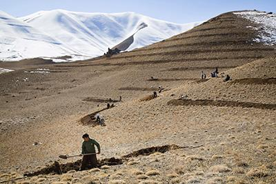 Farmers dig trenches in the Sareqol Valley in Afghanistan's Bamiyan Province. These trenches will protect the nearby irrigation canal from washing out with excess rainfall or snowmelt. Photo by Elie Gardner for Catholic Relief Services