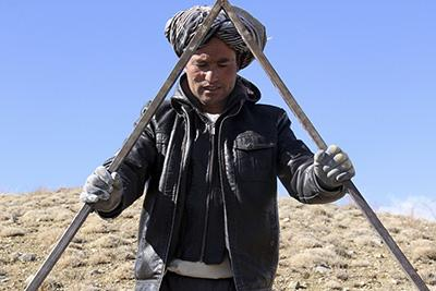 A day laborer surveys the land prior to digging trenches in the Sareqol Valley. The work is facilitated by CRS. Photo by Nikki Gamer/CRS
