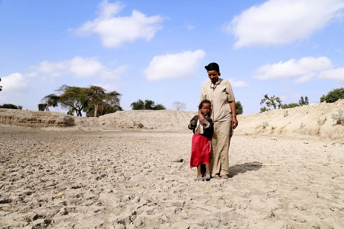 Badoo Fukura of Ethiopia stands at the bottom of a basin that used to be the community watering hole. Water from rains used to last 6 months, but in 2015, it lasted only 2 months. Photo by Nancy McNally/CRS