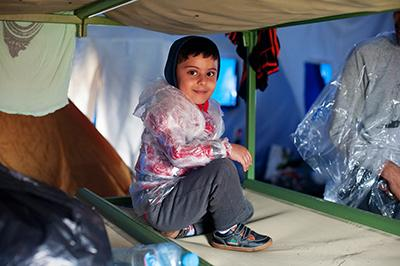 A Syrian child wears plastic bags in preparation for the wet journey to the Hungary border. Photo by Kira Horvath for CRS