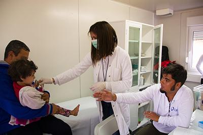 Dr. Sandra Mrdja examines a sick Syrian child with help from translator Kemal El Shairy, at the Vasariste refugee aid point in Kanjiza. Photo by Kira Horvath for CRS