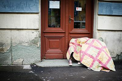Refugees passing through Belgrade sleep on the street, seeking warmth under a quilt. Rain and cold temperatures have made this already miserable journey much harder for the thousands feeing their homelands for Europe. Photo by Kira Horvath for CRS