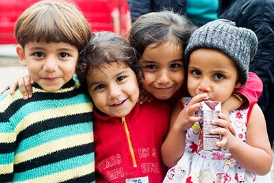 A group of Syrian children pose for a photo at a park near the Belgrade bus station. Photo by Kira Horvath for CRS