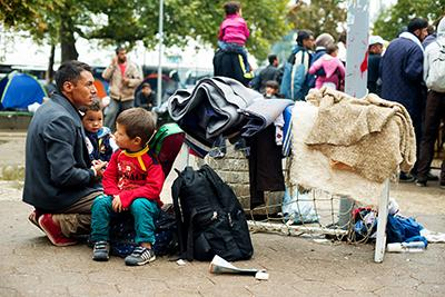 A refugee family waits for transportation to the Hungarian border at a park near the Belgrade bus station. Photo by Kira Horvath for CRS