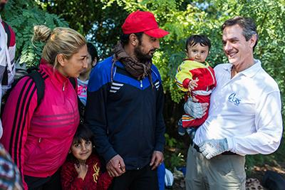 CRS Chief Operating Officer Sean Callahan holds 11-month-old Siad from Syria as his family prepares to cross the border from Serbia into Croatia. The family of five hopes to reach Germany. Photo by Andrew McConnell for CRS