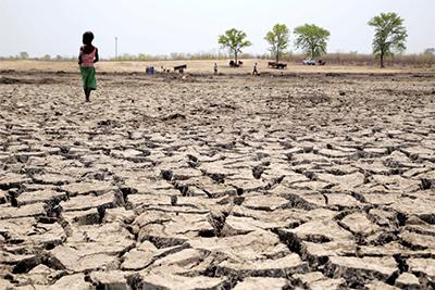 A child walks across the dried-out basin of what used to be a watering hole. Zimbabwe has been hit hard by the effects of El Niño and climate change, which has resulted in an extended drought. Photo by Nancy McNally/CRS