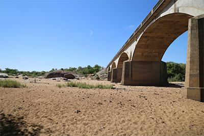 Bridges that once stood above rushing rivers now arch over nothing but sand. Many seasonal rivers in Zimbabwe dry up at certain times every year, but since the drought even perennial rivers have evaporated. Photo by Nancy McNally/CRS