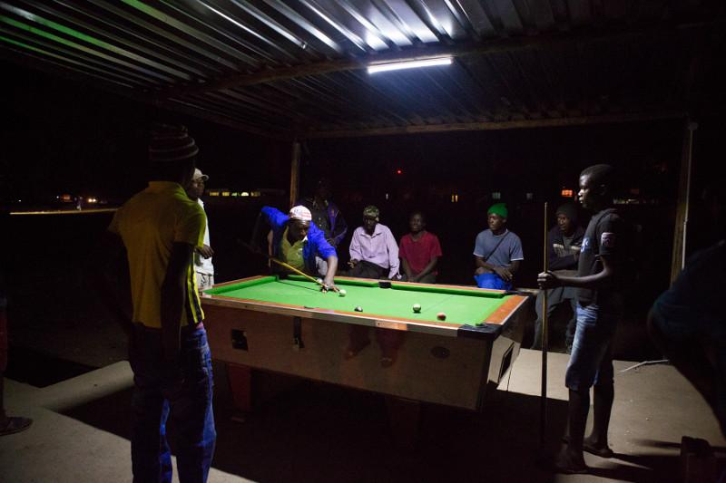 In Beitbridge, Zimbabwe, young men play billiards outside under a single light. Photo by Elie Gardner for CRS