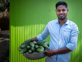 Man from Bangladesh holds a basket of vegetables
