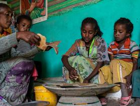 Woman and children from Ethiopia share dinner