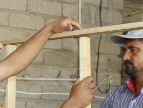 Local volunteers, most of them from the displaced community in northern Iraq, are trained by CRS' building engineers on basic construction and installing doors and windows in buildings that have become temporary shelters. Photo by Kim Pozniak/CRS