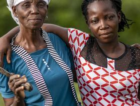 Nora Tolee and Martha Yelekor farm cassava with their neighbors in Nimba County, Liberia.