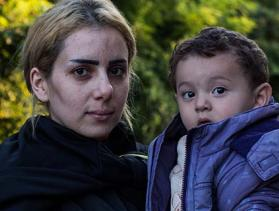 Serbian woman carrying her son