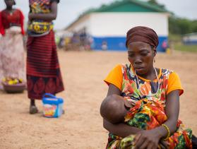 woman holding child during food distribution in Sierra Leone