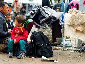 Serbian refugee man and sons wait near bus station