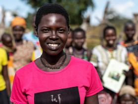 Woman from Uganda stands in front of group of people smiling at camera
