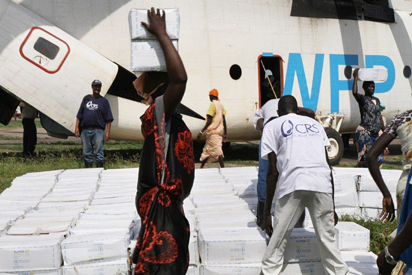 CRS staff unload food from a World Food Programme helicopter, and distributing it among families who have been displaced and affected by ongoing violence. Photo by Donal Reilly/CRS